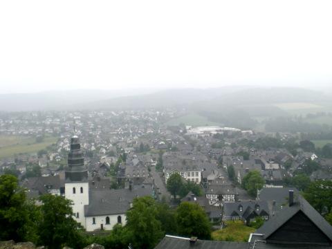 Ein dunstiger Juni-Morgen: Eversberg mit der St.-Johannes-Evangelist-Pfarrkirche