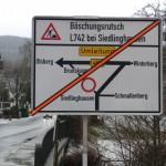 Sobald die Bauarbeiten beginnen, wird das rote Band abgezogen. Schild aus Richtung Elpe/Altenfeld kommend am Zusammenfluss von Neger und Namenlose in Siedlinghausen.