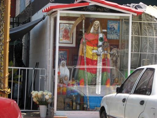 La hermana negra (die schwarze Schwester) – ein Schauglaskasten in Nezahualcoyotl. Der Volksglaube sagt, dass das Leben eben auch eine dunkle Seite hat. Wie finster die sein kann, ist wohl auch immer eine Frage des Standortes.