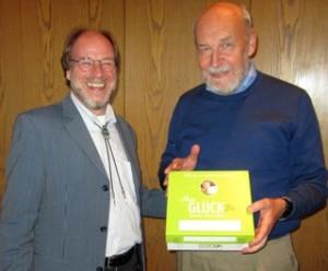 Detlef Träbert (links) wünscht seinem Nachfolger Jonas Lanig mit einer Schachtel voller Glück viel Erfolg in seinem neuen Amt. (Foto: © Aktion Humane Schule)