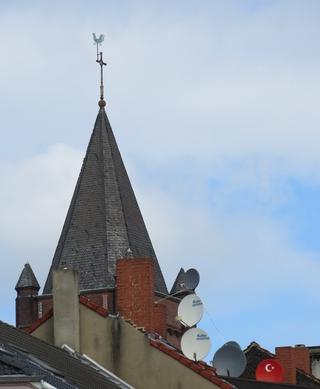 Kirchturm und Satellitenschüsseln