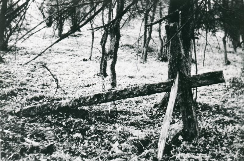 """Das """"Mescheder Sühnekreuz"""" zum Gedenken an 80 ermordete """"russische Zwangsarbeiter"""" nach seiner Ausgrabung im November 1964 mit den Spuren von Äxten, Feuer, Erdlagerung seit 1947 sowie verwitterter Inschrift (Archiv Peter Bürger)."""