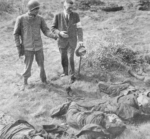 Ein US-Soldat zeigt Anfang Mai 1945 dem Warsteiner Bürgermeister Peter Struif die 71 Leichen der im Langenbachtal ermordeten Menschen (Repro Archiv P. Bürger; Aufnahme von U. Hillebrand in den 1980er Jahren bei der US-Army angefordert).