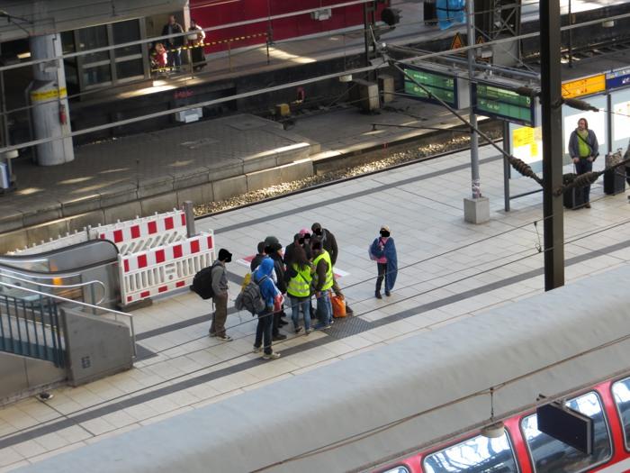 """Helfer ordnen auf einem deutschen Bahnhof den """"ungeordneten Flüchtlingsstrom"""". (foto: zoom)"""