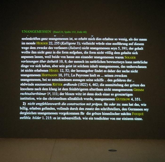 In einem kleinen Filmkubus scrollen vorne, links und rechts die Worteinträge über die Wände. Hinsetzen. Verweilen. Gucken. Denken. Erlebnis.